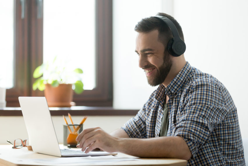 Smiling bearded man in headphones looking on laptop and typing